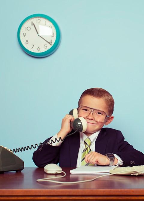 Un enfant déguisé en patron qui répond au téléphone