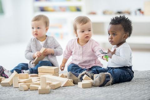 3 enfants jouant à un jeux de construction en bois